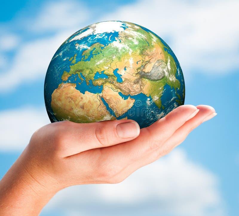 A mão da pessoa guarda o globo. imagens de stock royalty free