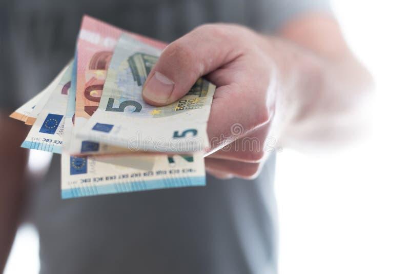 Mão da pessoa masculina que cede euro- cédulas imagens de stock