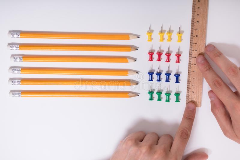 A mão da pessoa que arranja lápis e multi percevejos coloridos fotografia de stock royalty free