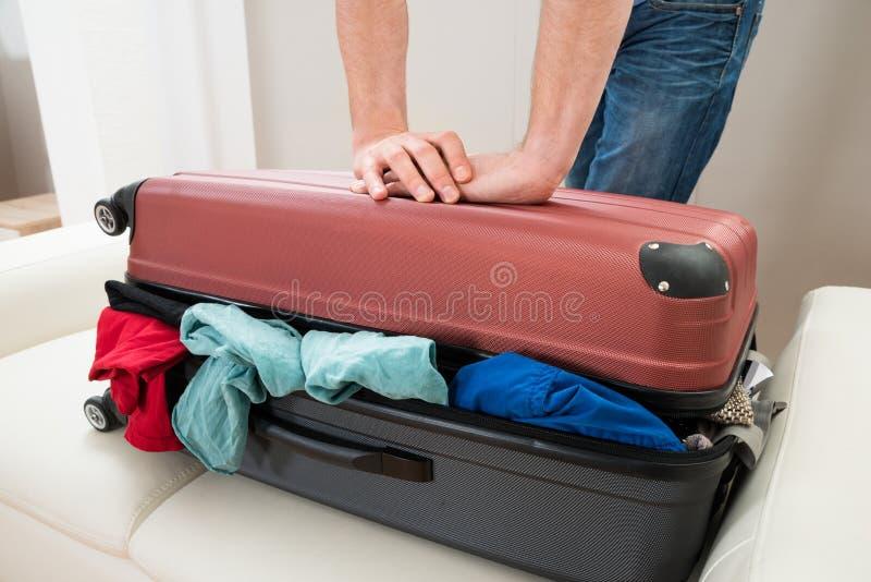 Mão da pessoa que tenta fechar a mala de viagem fotos de stock royalty free