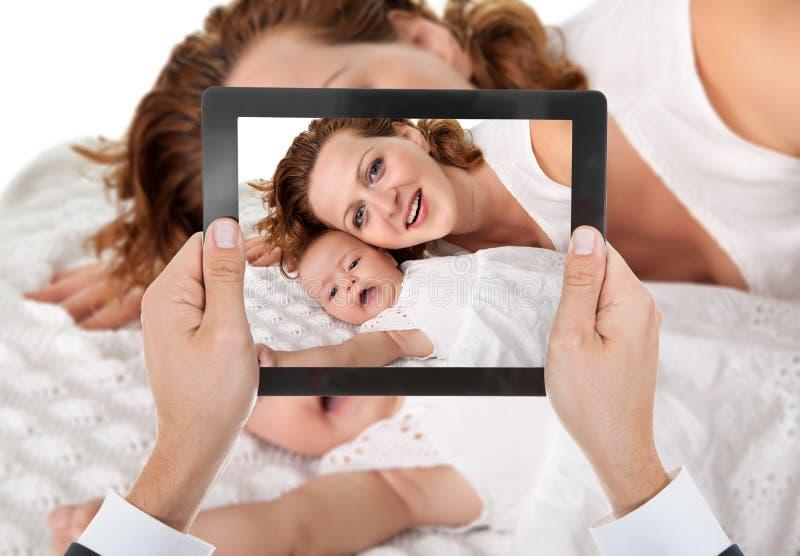 Mão da pessoa que toma a foto da mãe com bebê fotos de stock