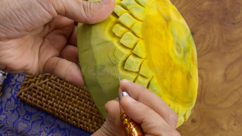 A mão da senhora que crafting a abóbora em um teste padrão floral Estilo tailandês foto de stock