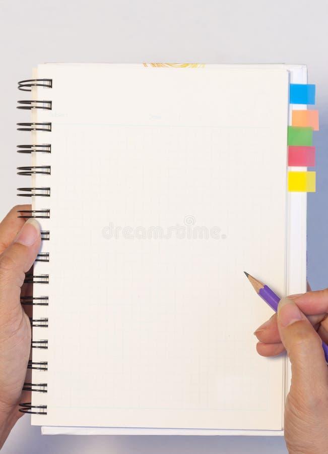 A mão da senhora que mantém o lápis pronto para escrever um caderno vazio com memorando pegajoso da nota imagem de stock royalty free