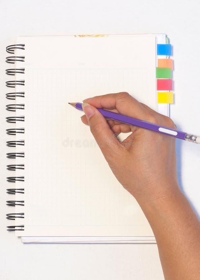 A mão da senhora que mantém o lápis pronto para escrever um caderno vazio com memorando pegajoso da nota fotos de stock royalty free