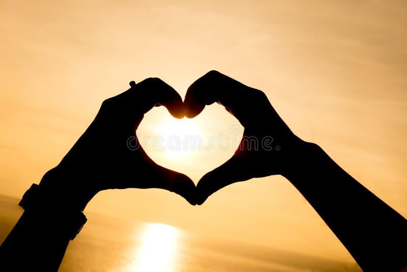 Mão da silhueta que faz a forma do coração com por do sol fotografia de stock royalty free