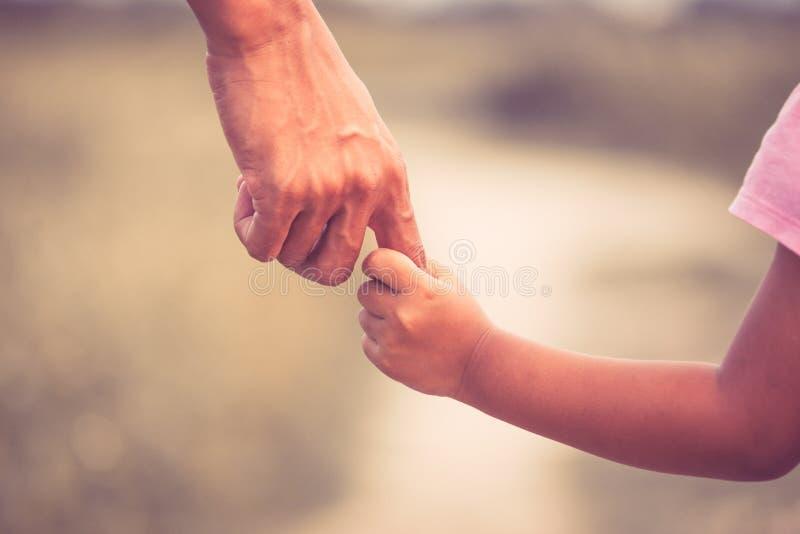 Mão da terra arrendada do pai e da filha junto fotos de stock