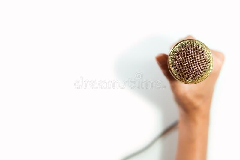 Mão da vista superior que guarda o microfone no fundo branco fotografia de stock royalty free