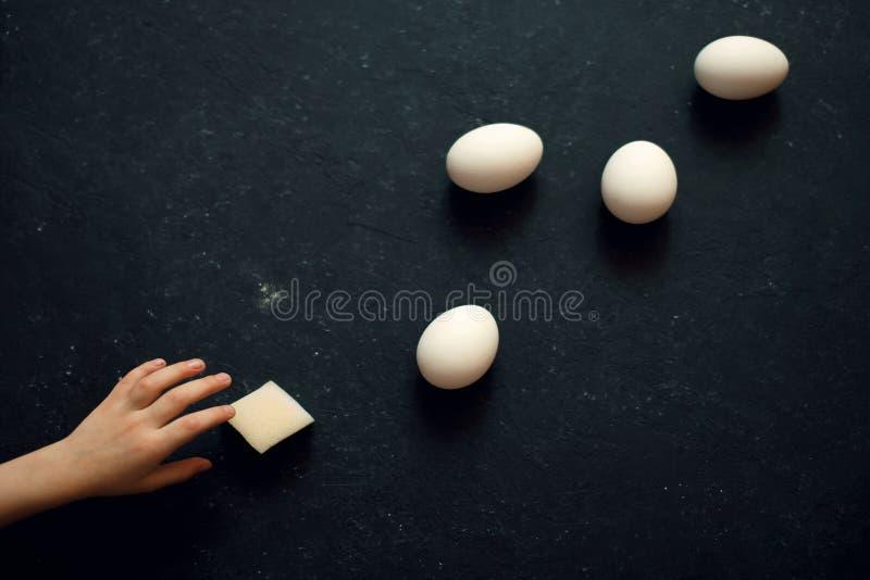 A mão das crianças alcança para os ovos foto de stock