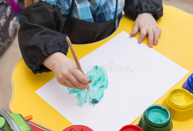 A mão das crianças com uma escova para tirar, a criança tira com pinturas e escova no papel fotos de stock