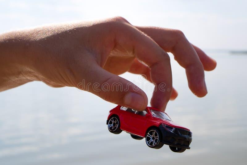 A mão das crianças que guarda um carro vermelho sobre o telhado sobre o cinza da água do mar, dia de verão durante fotos de stock royalty free