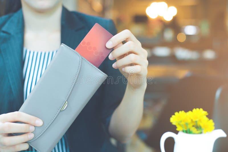 A mão das mulheres de negócio está puxando um cartão de crédito fora de uma carteira imagem de stock
