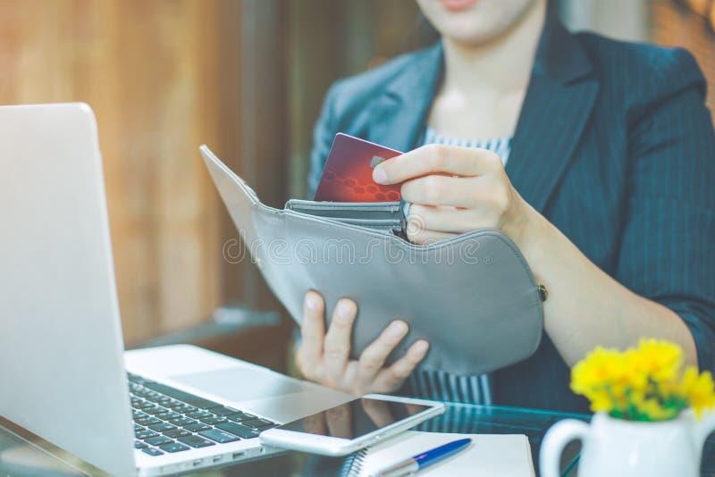 A mão das mulheres de negócio está puxando um cartão de crédito fora de uma carteira imagens de stock