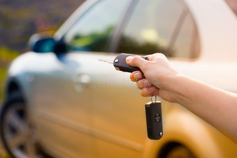 A mão das mulheres pressiona no alarme de controle remoto do carro foto de stock royalty free
