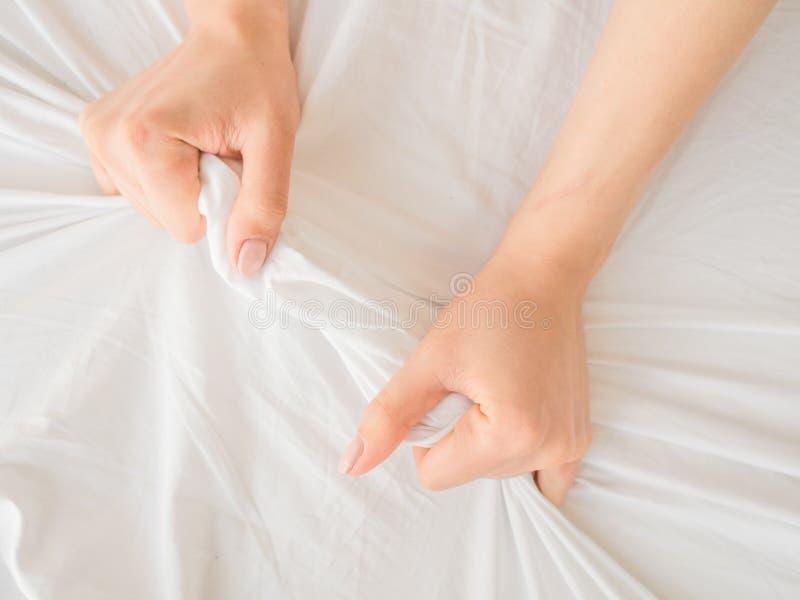 Mão das mulheres que puxam as folhas brancas na luxúria e no orgasmo imagem de stock