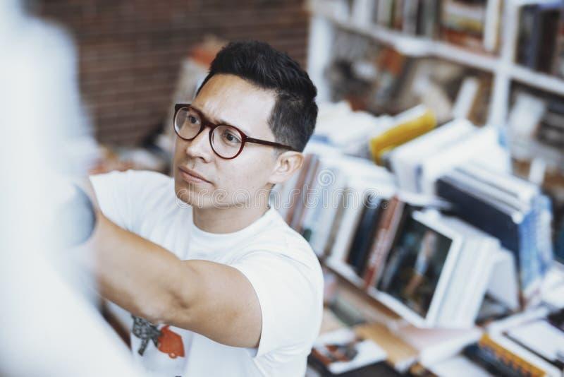 Mão de óculos atrractive nova do desenho do homem ao livro em uma biblioteca imagem de stock