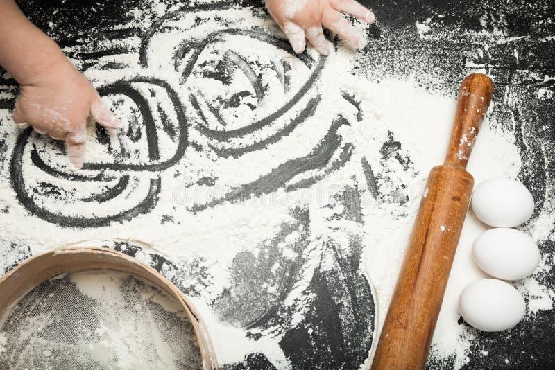 A mão de ?hild está jogando com farinha, ingredientes para cozer imagem de stock