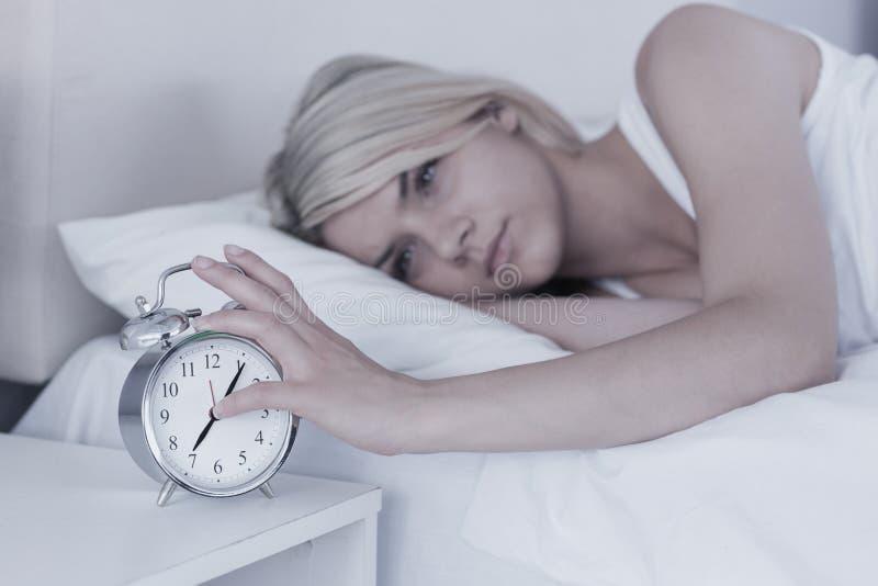 Mão de alargamento da mulher ao despertador na cama imagens de stock royalty free