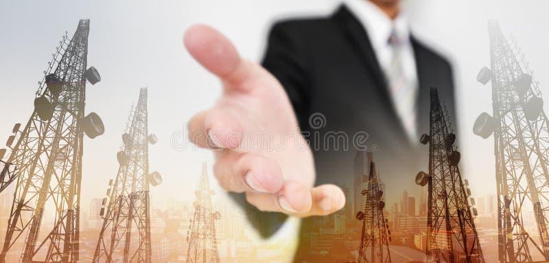 A mão de alargamento do homem de negócios, com telecomunicação da exposição dobro eleva-se e opinião da cidade no fundo do nascer imagens de stock