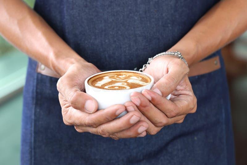 Mão de Barista que guarda a arte do latte do café com teste padrão o sino na cafetaria foto de stock royalty free
