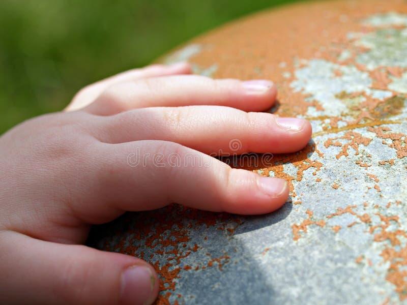 Mão de Childs na superfície oxidada foto de stock royalty free