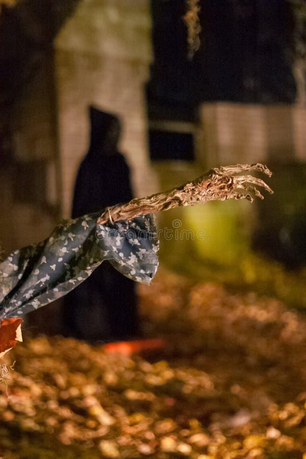 Mão de esqueleto com uma figura encapuçado escura no fundo imagem de stock royalty free