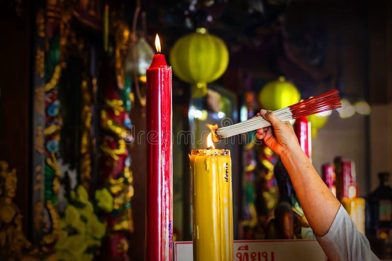 A mão de incenso ardente da mulher cola antes de rezar no templo fotografia de stock