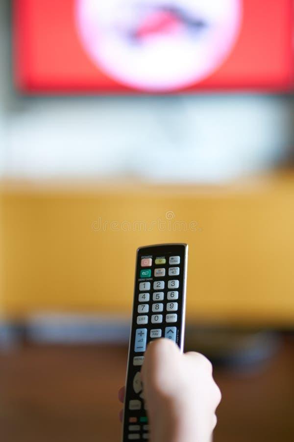 A mão de Kidque guarda um controlador remoto da tevê imagens de stock