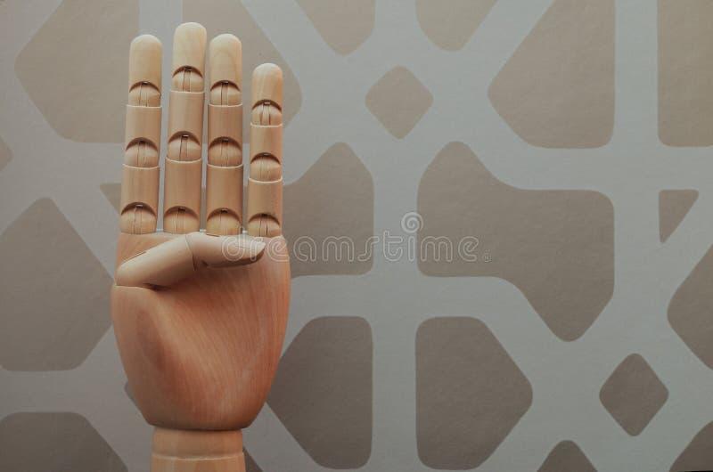 A mão de madeira articulada com quatro dedos aumentou em alusão ao número quatro fotografia de stock