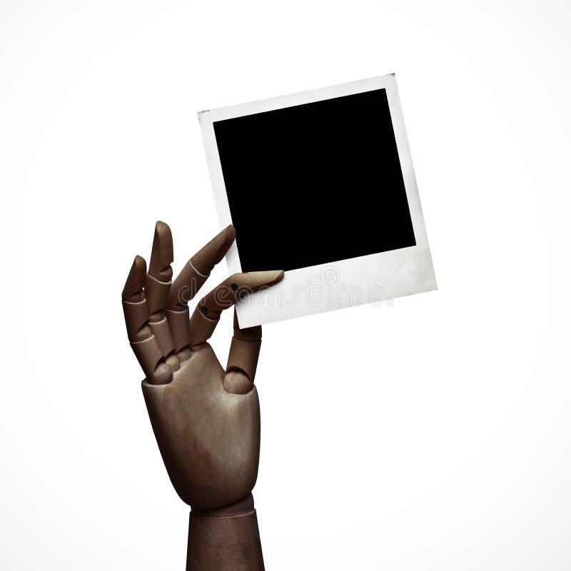 Mão de madeira escura com quadro do polaroid imagens de stock