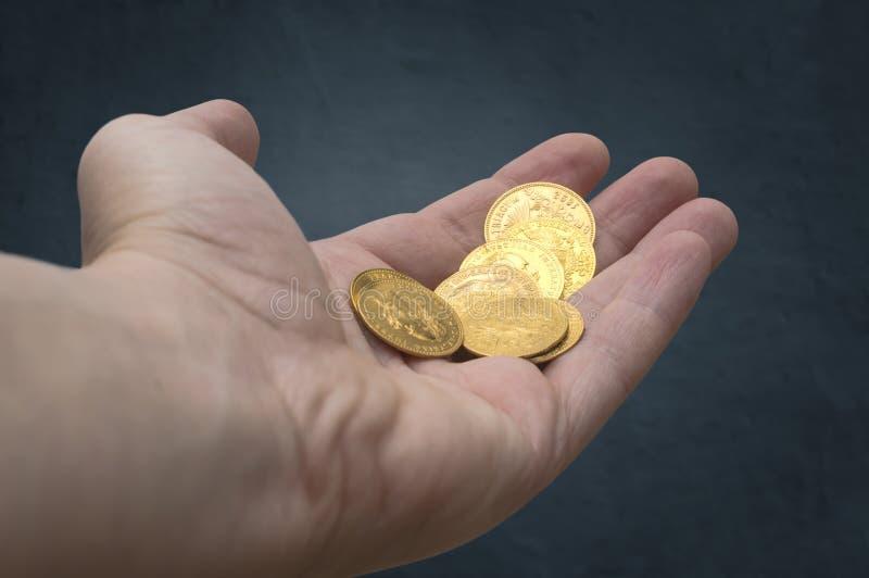Mão de moedas douradas fotografia de stock royalty free