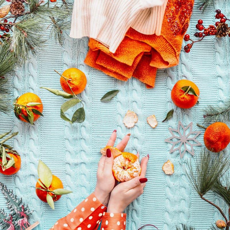 Mão de mulher com tangerinas em cobertor de malha azul com suéter de laranja e ramos de abeto, vista superior Hora de Natal imagens de stock royalty free