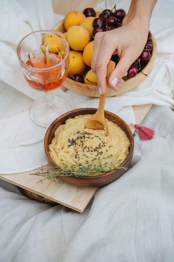 Mão de mulher esfregando humus com colher fotos de stock royalty free