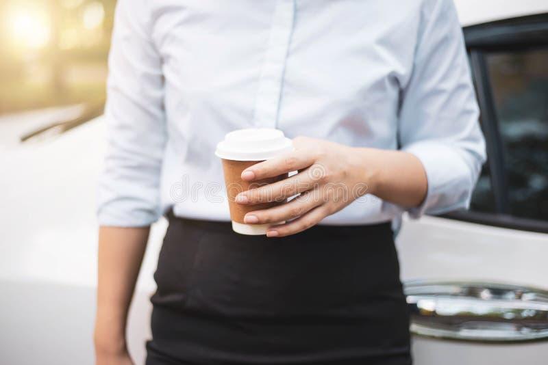 A mão de mulher de negócio que guarda um copo de café para levar embora imagem de stock