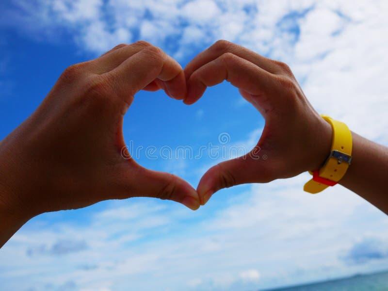 Mão de mulheres de Ásia e coração da fatura no céu azul fotografia de stock royalty free