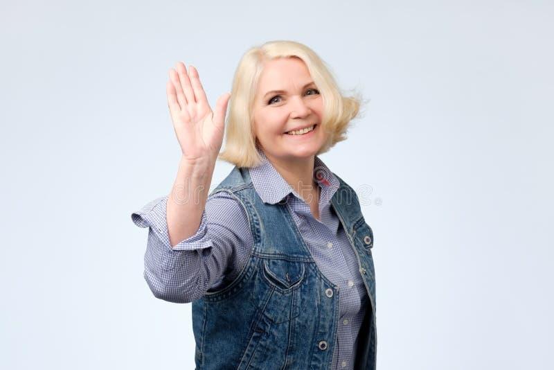 Mão de ondulação da mulher idosa que diz olá!, cumprimentando o amigo fotografia de stock