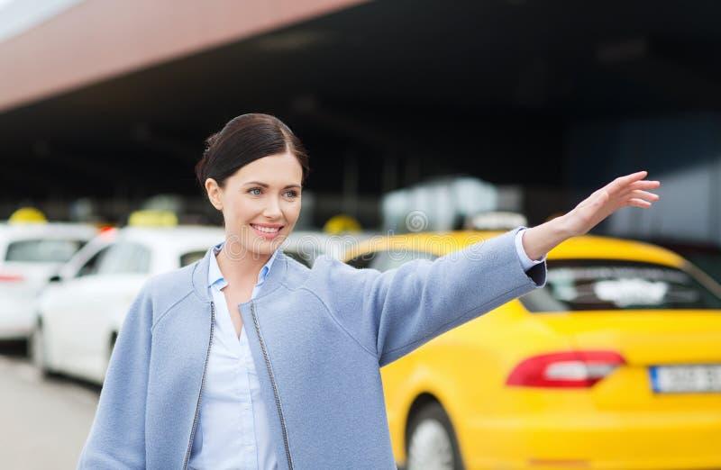 Mão de ondulação de sorriso da jovem mulher e táxi de travamento imagens de stock