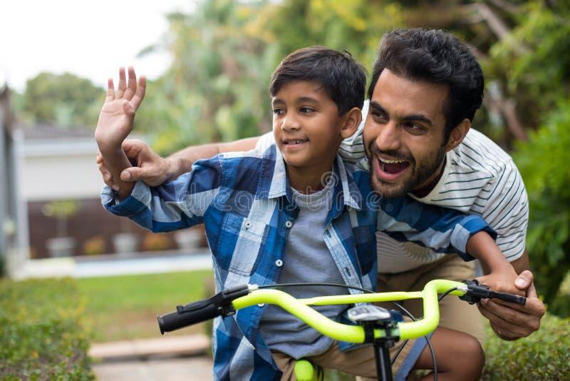 Mão de ondulação do pai e do filho ao dar um ciclo imagem de stock royalty free
