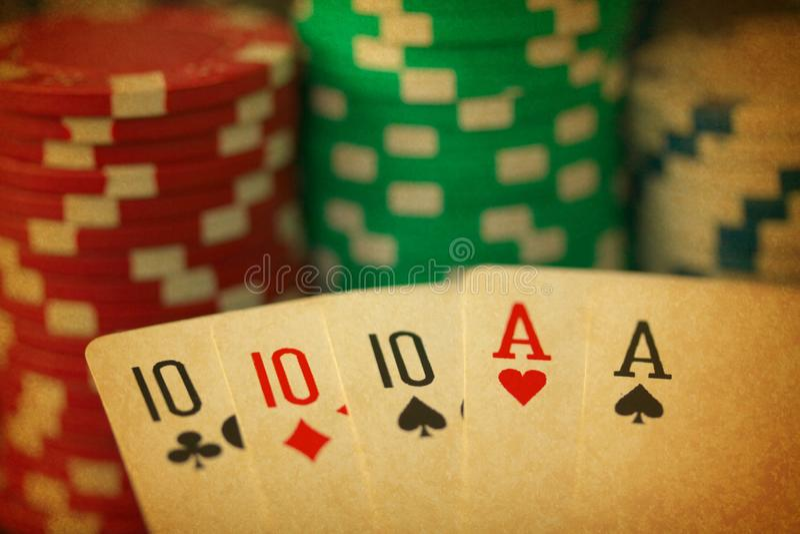 A mão de pôquer com os cartões e o jeton da casa completa lasca-se no fim acima no backgrund preto - feito como uma foto velha fotografia de stock royalty free