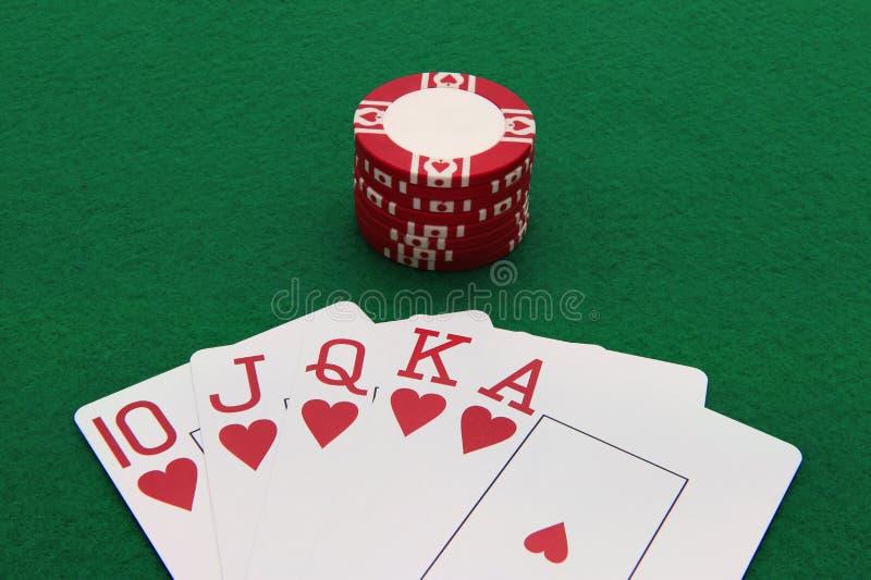 Mão de pôquer com a microplaqueta do casino na tabela verde fotografia de stock