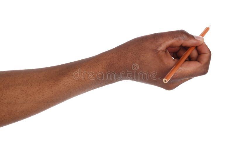 Mão de pele escura que guarda o lápis preto imagens de stock