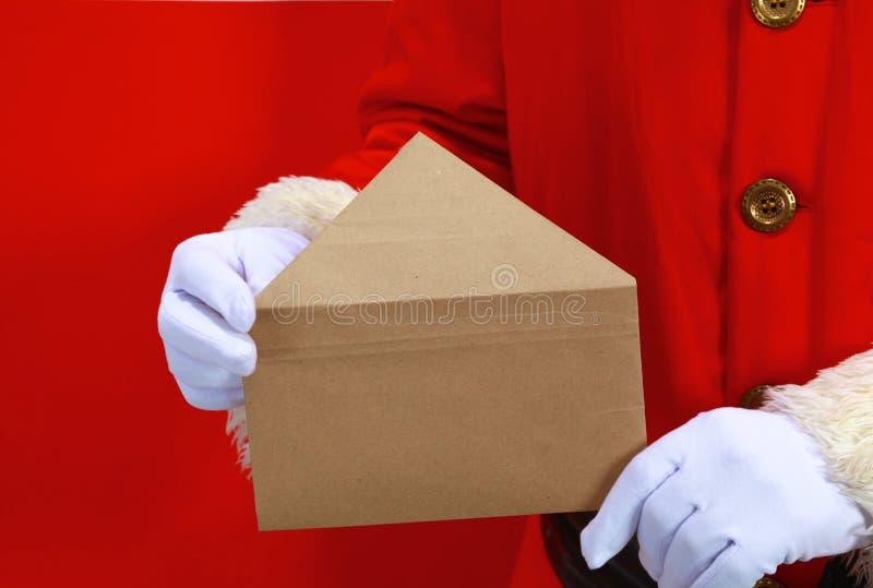 Mão de Santa Claus com uma letra em um fundo vermelho foto de stock