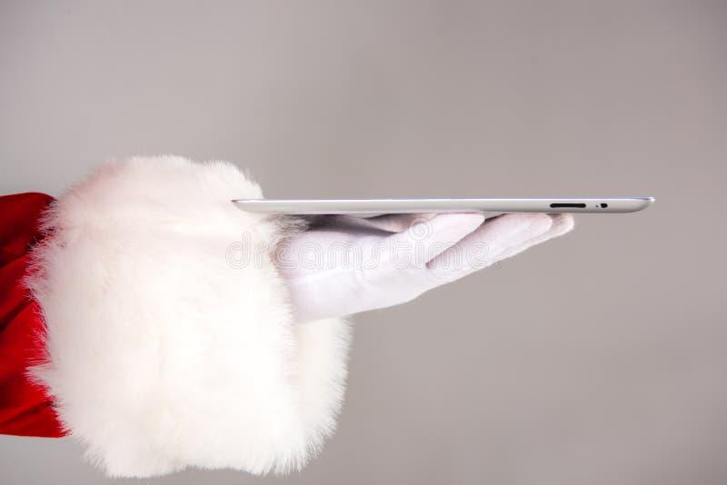 Mão de Santa Claus que mostra a tabuleta digital foto de stock