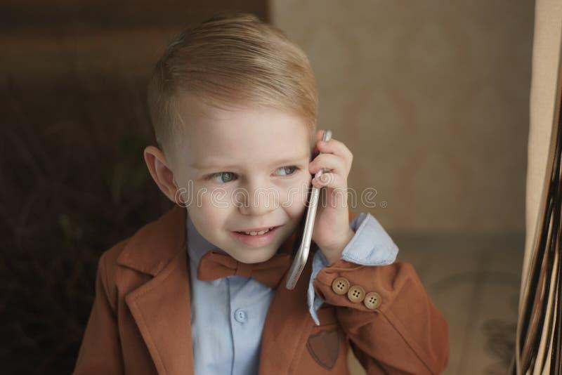 Mão de sorriso do menino da criança da beleza que guarda o telefone celular ou que fala o smartphone fotografia de stock