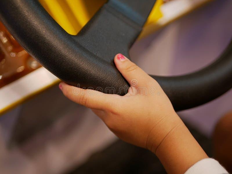 Mão de um bebê pequeno que guarda sobre um volante de um jogo de arcada decondução que aprende como fazê-lo imagens de stock royalty free