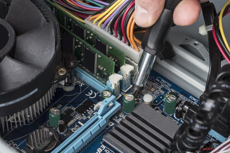 A mão de um coordenador de computador com uma chave de fenda repara o m fotografia de stock royalty free