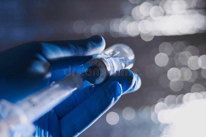 A mão de um doutor nas luvas médicas azuis que guardam a seringa e a vacina foto de stock royalty free