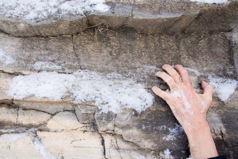 A mão de um homem adere-se a uma borda em uma pedra Balanç coberto com a neve imagem de stock