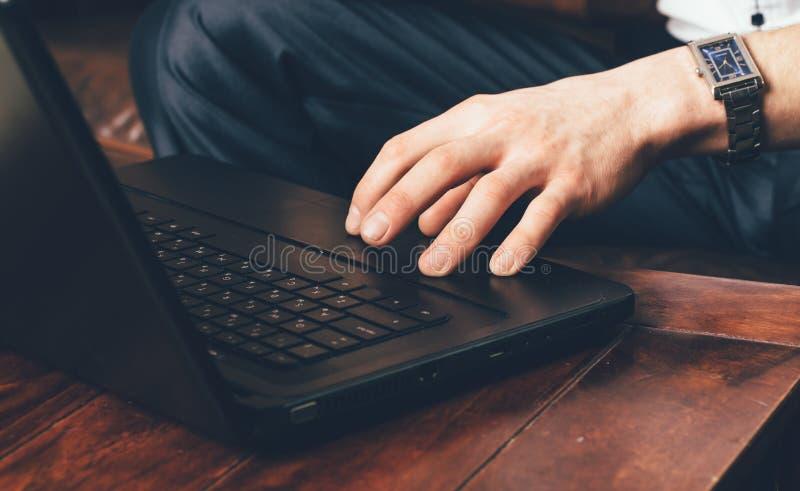 A mão de um homem com um relógio de pulso está no touchpad do portátil O homem de negócios trabalha em casa em sua própria sala imagem de stock