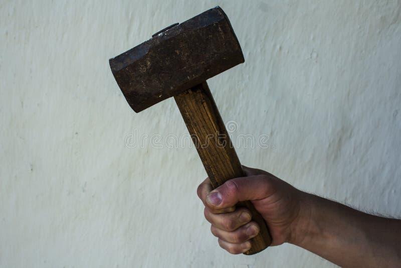 A mão de um homem com um grande martelo fotos de stock royalty free