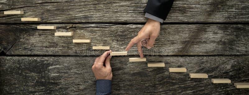 Mão de um homem de negócios que apoia uma etapa de madeira para seu colega foto de stock